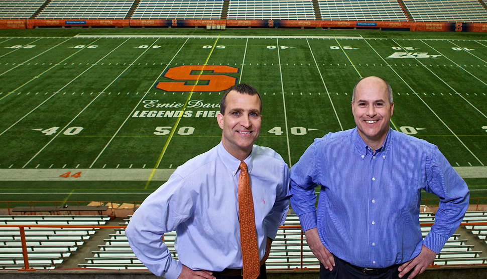 Syracuse University's Risk Management and Associate Athletic Director in front of a football field.